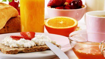 Frühstückstisch mit Knäcke, Orangensaft, Honig, Obst, Kaffee